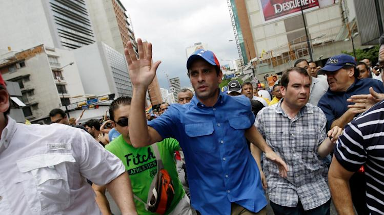 Opposition leader Henrique Capriles greets supporters during an opposition May Day march in Caracas, Venezuela, Wednesday, May 1, 2013. Venezuelans filled the streets of the capital Wednesday in rival marches by the opposition and the government less than a day after a brawl on the floor of congress injured several opposition lawmakers. (AP Photo/Fernando Llano)