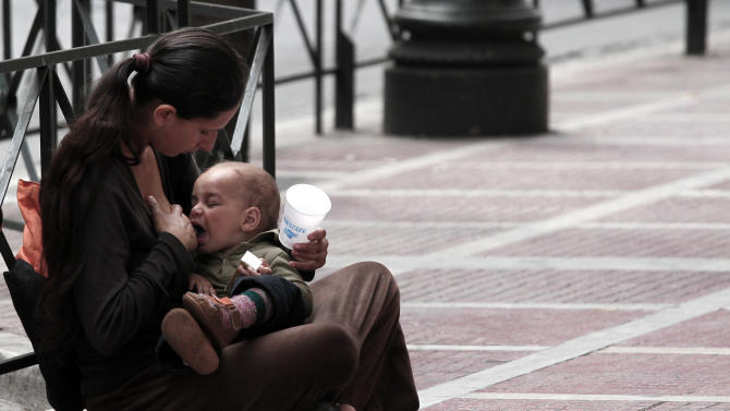 A woman begs for alms, as she feeds her baby in central Athens on Tuesday May 29, 2012.  The four biggest Greek banks received 18 billion euros (22.6 billion USD) in rescue funds on May 28, 2012 to help reinforce their capital bases, a Hellenic financial stability fund source said. National Bank, the biggest Greek lender, has received 7.43 billion euros, Piraeus bank 4.7 billion, Eurobank 3.97 billion and Alpha 1.9 billion, the official said.(AP Photo/Dimitri Messinis)