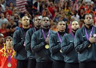 US players listen to their national anthem on the podium after winning the gold medal in the London 2012 Olympic Games men&#39;s basketball competition at the North Greenwich Arena in London. The US won the gold medal followed by the silver to Spain and the bronze to Russia
