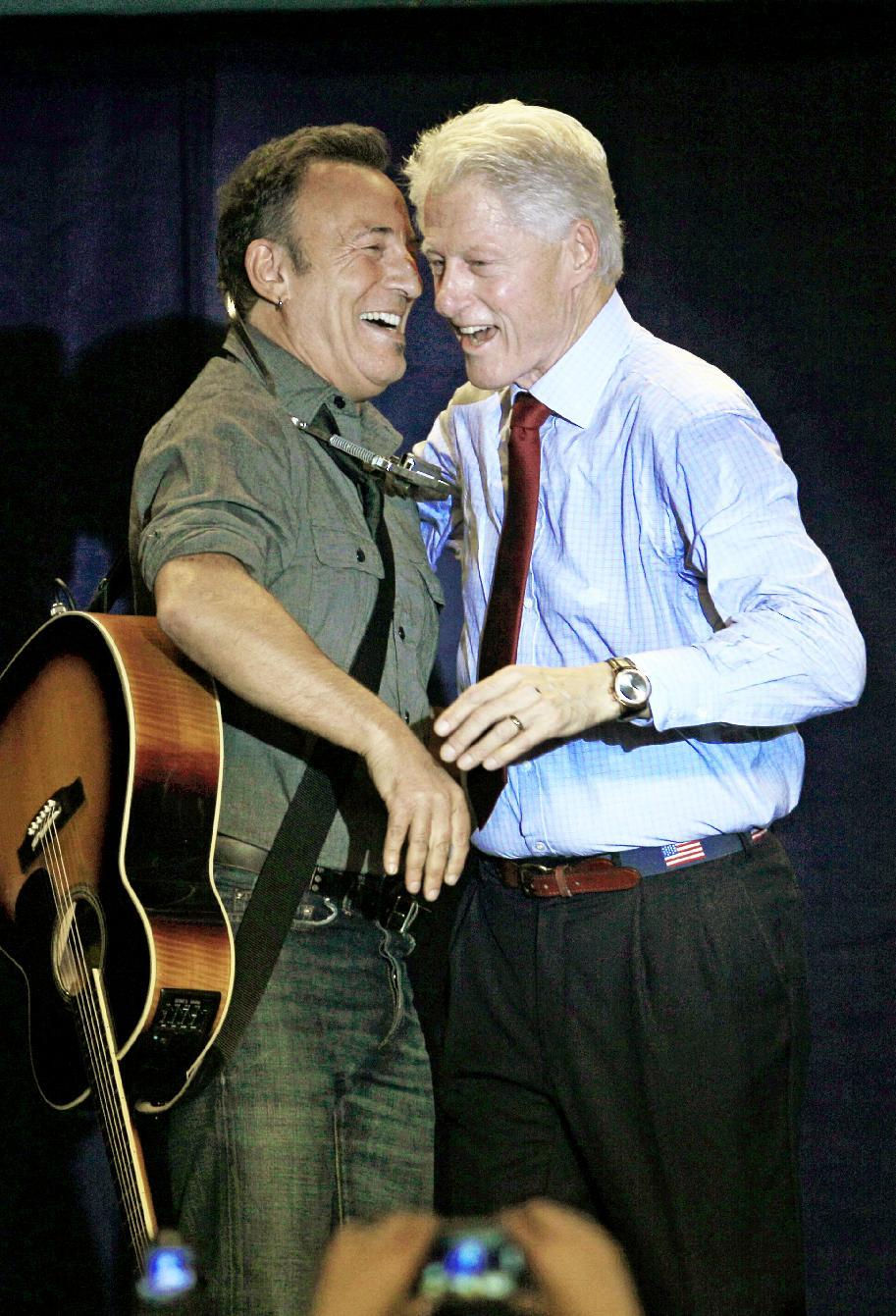 Former President Bill Clinton, right, laughs with singer/songwriter Bruce Springsteen during a campaign event for President Barack Obama, Thursday, Oct. 18, 2012, in Parma, Ohio. (AP Photo/Tony Dejak)
