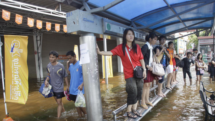 People stand on benches at a bus stop at Phisi Charoen district  in Bangkok on Wednesday, Nov. 2, 2011. (AP Photo/Sakchai Lalit)