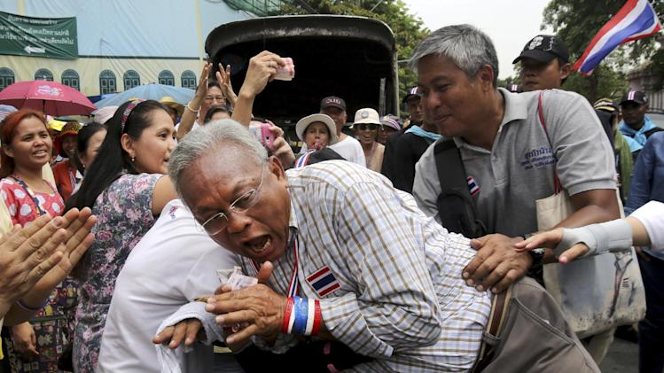 Leader of anti-government protesters Suthep Thaugsuban reacts as he is hugged by a supporter during a march in Bangkok, Thailand, Monday, May 19, 2014. Thailand's political crisis deepened last week when the Constitutional Court removed Prime Minister Yingluck Shinawatra for nepotism along with nine Cabinet members in a case that many viewed as politically motivated. Protesters say Yingluck's removal is not enough, though. She was simply replaced by Niwattumrong, who was a deputy premier from the ruling party. (AP Photo/Sakchai Lalit)