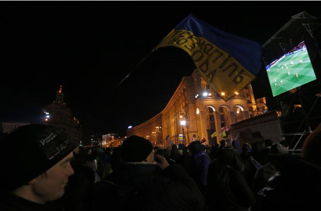 Pro-European integration protesters watch the Champions League soccer match between Manchester United and Shakhtar Donetsk on a screen in Independence Square in Kiev