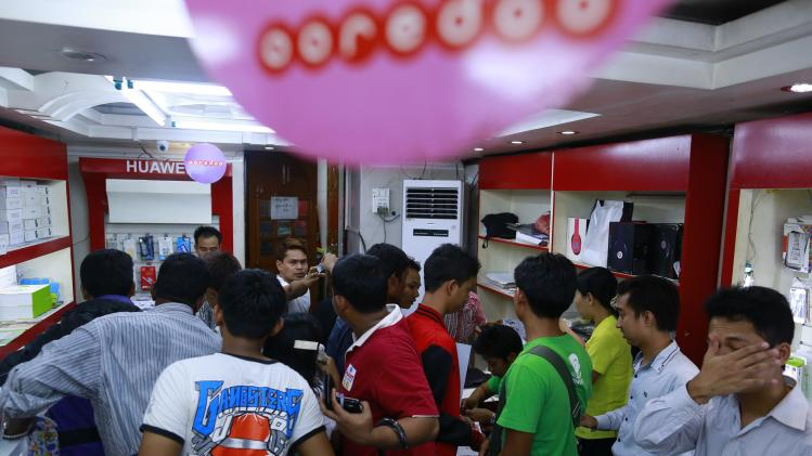 People gather in a shop to buy Sim cards from Qatar's Ooredoo at a phone shop in Yangon