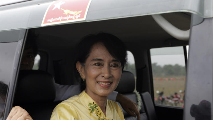 FILE - In this April 17, 2012, file photo, Myanmar pro-democracy leader Aung San Suu Kyi greets her supporters from her vehicle on the way to visiting Kawhmu township in Yangon, Myanmar, on New Year's Day. The European Union's suspension of economic sanctions against Myanmar is riling exiled activists, who are urging the United States to press for further reforms by the dominant military before following suit. The activists' opposition has exposed differences with democracy leader Suu Kyi, whose cause they have championed for more than two decades and helped drive the sanctions in the first place. (AP Photo/Khin Maung Win, File)