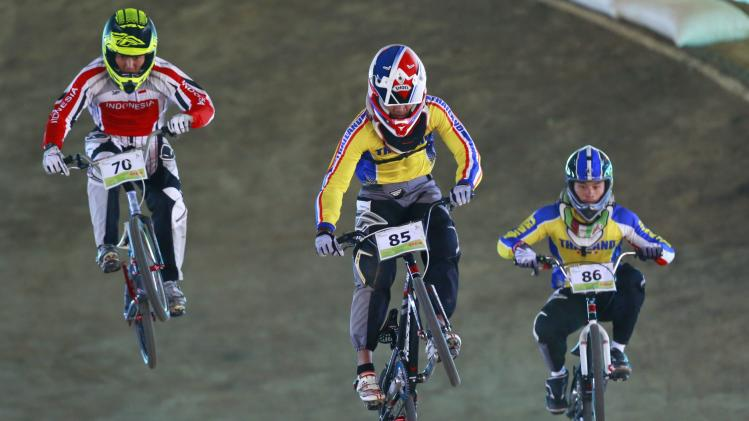 Thailand's Panyapol and Jukrapech compete next to Indonesia's Saputra at the men's BMX Cross cycling final during the 27th SEA Games in Naypyitaw