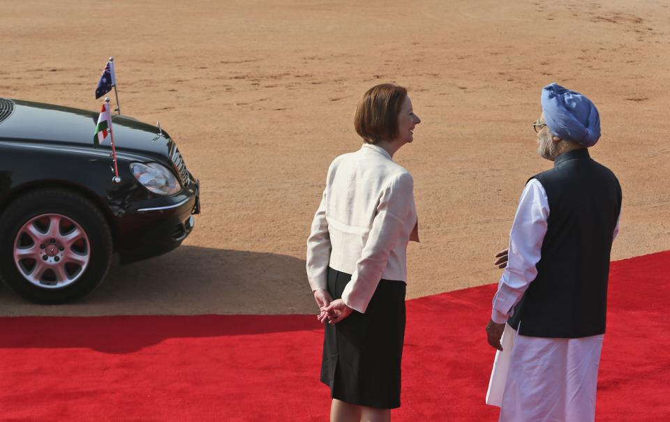 Indian Prime Minister Manmohan Singh, right, talks with his Australian counterpart Julia Gillard on her arrival at the Indian Presidential palace for ceremonial reception, in New Delhi, India , Wednesday, Oct. 17, 2012. (AP Photo/ Manish Swarup)