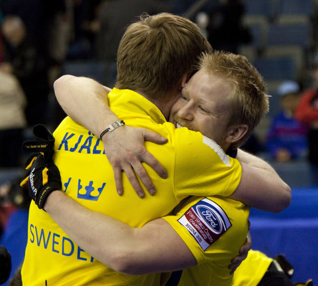 Swedish skip Niklas Edin (R) hugs lead Viktor Kjaall as they celebrate their  7-6 win over Norway in the bronze medal match at the Ford World Men's Curling Championships in Regina, Saskatchewan, April