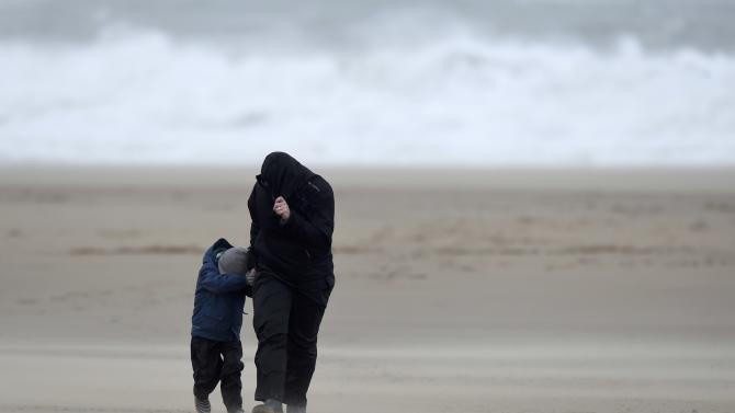 A man and his son struggle to walk on the beach at Broad Haven, Wales