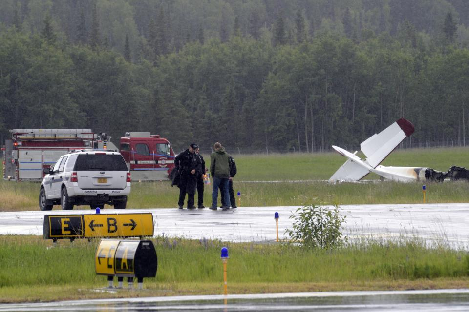 Investigators look at the remains of a fixed-wing aircraft that was engulfed in flames Sunday July 7, 2013 at the Soldotna Airport in Soldotna, Alaska. No survivors were located and it is unknown how many people were on board. (AP Photo/Peninsula Clarion, Rashah McChesney)