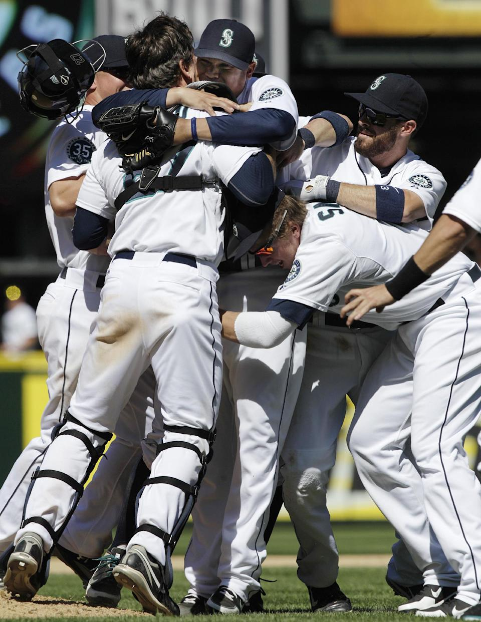 Seattle Mariners pitcher Felix Hernandez is mobbed by teammates, including catcher John Jaso, after he threw a perfect game against the Tampa Bay Rays, in a baseball game Wednesday, Aug. 15, 2012, in Seattle. The Mariners won 1-0. (AP Photo/Ted S. Warren)