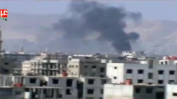 This image taken from video obtained from Ugarit News on Friday, Feb. 8, 2013, which has been authenticated based on its contents and other AP reporting, show smoke rising from fighting near a main highway in Damascus, Syria. Rebels pushed forward in their battle with the Syrian army in northeastern Damascus on Friday, shutting down a main highway with a row of burning tires, activists said. A number of rebel brigades launched a campaign Wednesday to attack regime checkpoints along the highway and have been clashing in the area since. The government has responded by shelling number of rebel areas nearby. (AP Photo/Ugarit News via AP video)