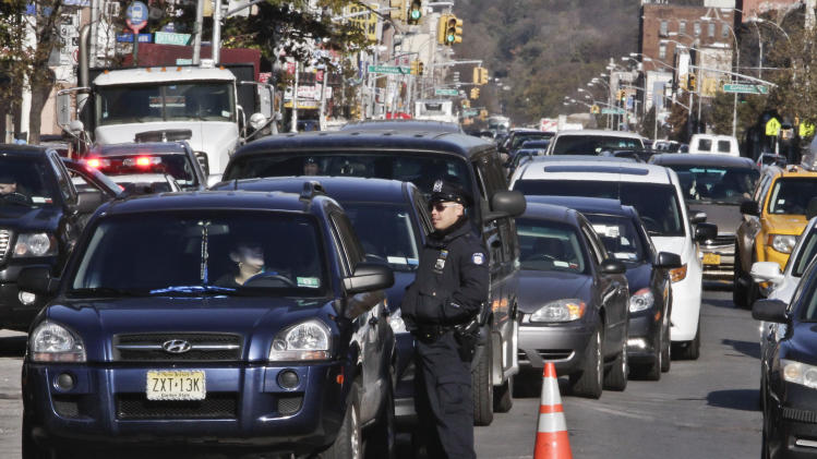 Police direct cars to gas pumps outside a gas station on Friday, Nov. 9, 2012 in the Brooklyn borough of New York.  Police were at gas stations to enforce a new gasoline rationing plan that lets motorists fill up every other day that started in New York on Friday morning. (AP Photo/Bebeto Matthews)