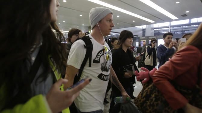 Lotus driver Kimi Raikkonen, center, of Finland is surrounded by his fans upon his arrival at Pudong International Airport ahead of Chinese Formula One Grand Prix in Shanghai, China Thursday, April 11, 2013. (AP Photo/Eugene Hoshiko)