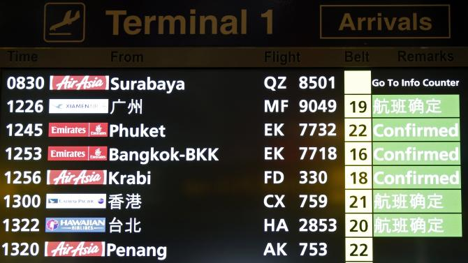 A flight information signboard shows the status of AirAsia flight from Indonesian city of Surabaya to Singapore at Changi Airport in Singapore