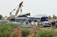 A crane lifts the mangled remains of a coach of the Bangalore-bound Hampi Express after it collided with a stationary goods train near Penneconda town in Ananthpur District, about 145 kms from Bangalore