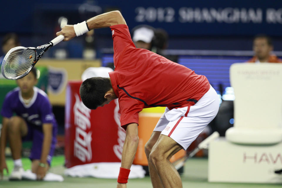 Novak Djokovic of Serbia smashes his racket after missing a game against Andy Murray of Britain during the men's singles final at the Shanghai Masters tennis tournament at Qizhong Forest Sports City Tennis Center in Shanghai, China, Sunday Oct. 14, 2012. (AP Photo/Eugene Hoshiko)