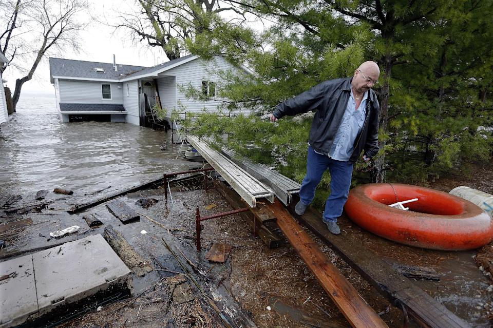 Mike Branchik returns to dry land using a make shift walkway from his home as the Illinois River floods homes Tuesday, April 23, 2013, in Peoria Heights, Ill. Floodwaters are rising to record levels along the Illinois River in central Illinois.   (AP Photo/Seth Perlman)