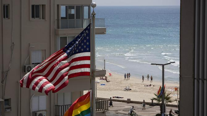 A U.S. flag is raised alongside a pride flag on the U.S. Embassy a day before the Gay Pride Parade in Tel Aviv, Israel, Thursday, June 12, 2014. In June, Tel Aviv celebrates its annual, week-long event that supports lesbian, gay, bisexual, transgender and their supporters, also known as the LGBT community. (AP Photo/Oded Balilty)