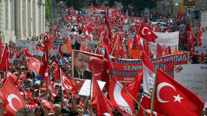 CORRECTS TO PRIME MINISTER - Supporters of Turkish Prime Minister Recep Tayyip Erdogan hold posters, banners and flags during a demonstration in Vienna, Austria, Sunday, June 23, 2013. Several thousand protesters gathered in Vienna to support Erdogan and his policy. (AP Photo/Herwig Prammer)