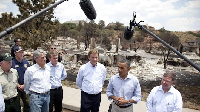 President Barack Obama speaks to the media as he tours the Mountain Shadow neighborhood devastated by wildfires, Friday, June 29, 2012, in, Colorado Springs, Colo. From left are, Tom Tidwell, U.S. Forest Service Chief, Sen. Mark Udall, D-Colo., Sen. Michael Bennet, D-Colo., Colorado Springs Mayor Steve Bach, the president, and Rep. Doug Lamborn, R-Colo. (AP Photo/Carolyn Kaster)