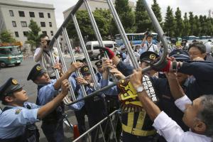 Police officers remove a steel fence as protesters…
