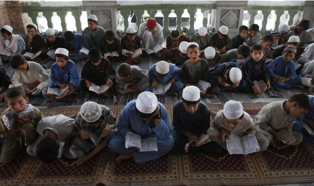 Afghan boys read the Quran during the Muslim holy month of Ramadan at a mosque in the city of Jalalabad, the provincial capital of Nangarhar province, east of Kabul, Afghanistan, Sunday, July 22, 2011