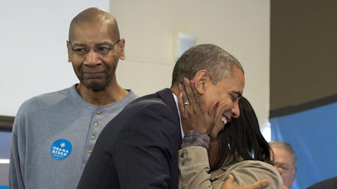 President Barack Obama is embraced by a volunteer as he visits a campaign office the morning of the 2012 election, Tuesday, Nov. 6, 2012, in Chicago. (AP Photo/Carolyn Kaster)