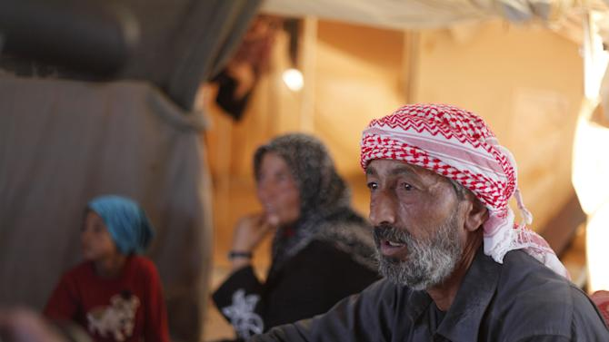 In this Tuesday, Sept. 11, 2012 photo, Ghassan Baradan, 50, a farmer who fled his southern restive border town of Daraa, Syria with his family in July, speaks during an interview at the Zaatari Refugee Camp, in Mafraq, Jordan. Jordan now hosts 200,000 Syrians, the largest number of refugees of any neighboring country. After months of delay, Jordan finally opened its first official refugee camp in July at Zaatari, near the border with Syria. (AP Photo/Mohammad Hannon)