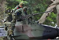 Taiwan soldiers climb on a tank during last year&#39;s drill simulating a Chinese military invasion in Tamshui. Taiwan has kicked off its biggest annual war game, testing its ability to defend of the capital Taipei against a Chinese attack and ward off a blockade of its main naval base