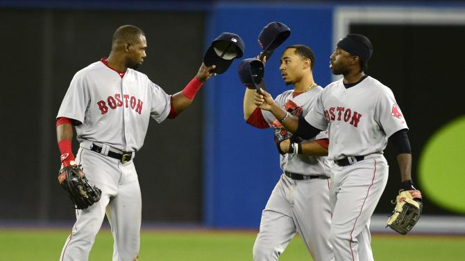 Boston Red Sox players Alejandro De Aza, left to right, Mookie Betts and Jackie Bradley Jr. celebrate their win over the Toronto Blue Jays after a baseball game, Thursday, July 2, 2015, 2015 in Toronto.  (Frank Gunn/The Canadian Press via AP) MANDATORY CREDIT