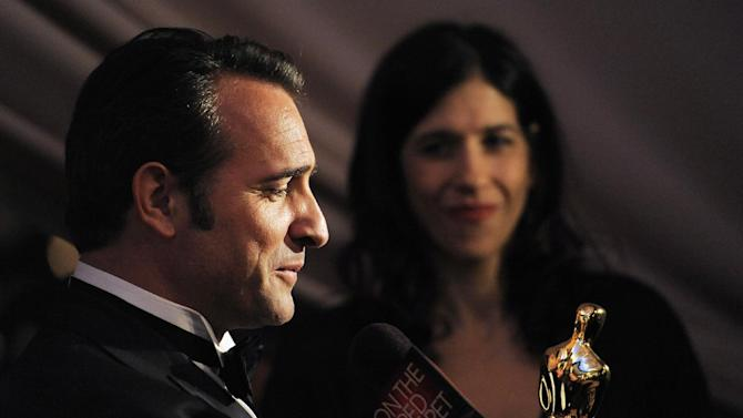 "Jean Dujardin winner of best actor for this work in ""The Artist"" looks at his Oscar award at the Governors Ball following the 84th Academy Awards on Sunday, Feb. 26, 2012, in the Hollywood section of Los Angeles. (AP Photo/Chris Pizzello)"