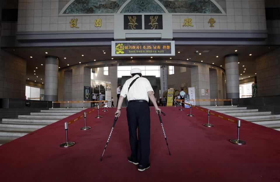 South Korean war veteran Moon Seung-joon (87) walks with canes at the War Memorial of Korea in Seoul, South Korea, Monday, June 25, 2012. People visit the War Memorial on Monday to mark of the 62nd anniversary of the Korean War Commemoration. (AP Photo/Lee Jin-man)