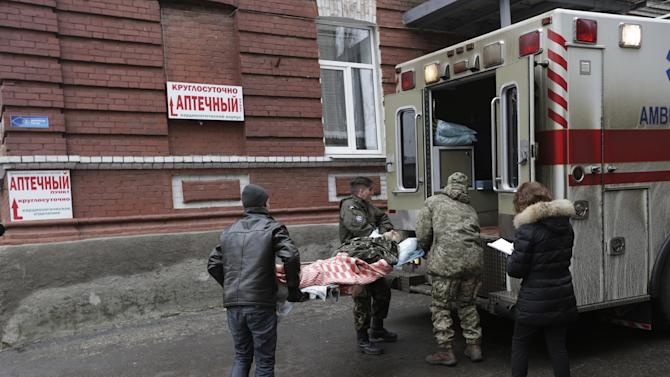 An injured soldier is loaded onto an ambulance outside of a hospital in the town of Artemivsk, Ukraine, Friday, Jan. 30, 2015. Fighting between government and Russian-backed separatist forces in eastern Ukraine has intensified in recent days as rebels seek to encircle the town of Debaltseve, which hosts a strategically important railway hub. (AP Photo/Petr David Josek)