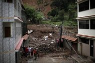 Residents watch after a landslide in Nova Friburgo, Rio de Janeiro state, Brazil, Saturday, Jan. 15, 2011. After four nights of torrential rains, mudslides have killed more than 500 people in the Rio de Janeiro area.