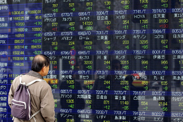 A man watches an electric price display of a securities firm in Tokyo, Wednesday, Jan. 16, 2013. Japans benchmark index toppled off a 32-month high Wednesday after its currencys downward slide went 