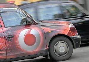 Vodafone branding is seen on the side of a London taxi in London