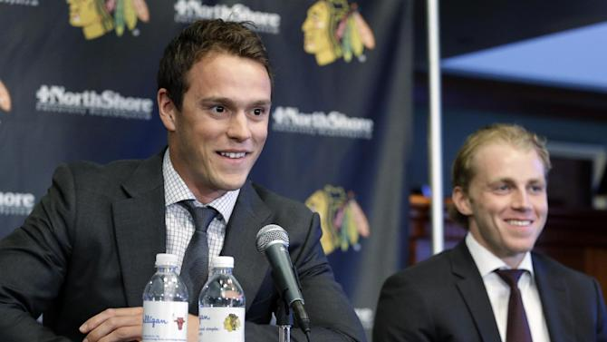 Chicago Blackhawks' Jonathan Toews, left, and Patrick Kane, smile as they listen to the media during a news conference at the United Center in Chicago, Wednesday, July 16, 2014. The Blackhawks recently agreed to eight-year contract extensions with for their star players