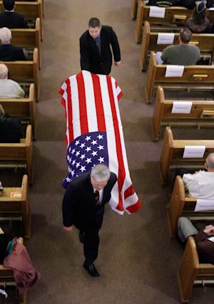 The flag covered casket of Artie Hodapp is carried down the center of St. Joseph Catholic Church during funeral services in Freeport, Ill., Wednesday, May 25, 2011. More than half a century after he died in Korea, the bones of the young soldier, Artie Hodapp, are returned after being matched with relatives' DNA. (AP Photo/Seth Perlman)