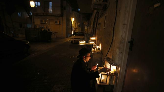 An Ultra-Orthodox Jewish man lights a candle on the seventh night of the holiday of Hanukkah in Jerusalem