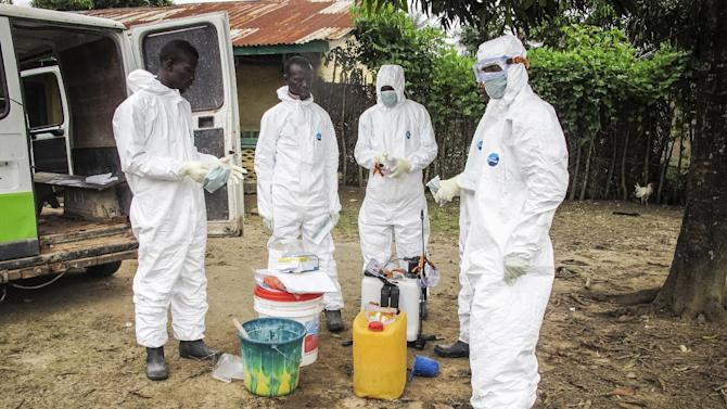 Health workers wears protective gears before entering the house of a person suspected to have died of  the Ebola virus in Port Loko Community situated on the outskirts of Freetown, Sierra Leone, Tuesday, Oct. 21, 2014. After emerging months ago in eastern Sierra Leone, Ebola is now hitting the western edges of the country where the capital is located with dozens of people falling sick each day, the government said Tuesday. So many people are dying that removing bodies is reportedly a problem. (AP Photo/Michael Duff)