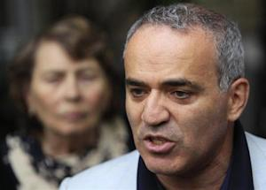 Former world chess champion and opposition leader Kasparov speaks to the media after walking out of a court building in Moscow