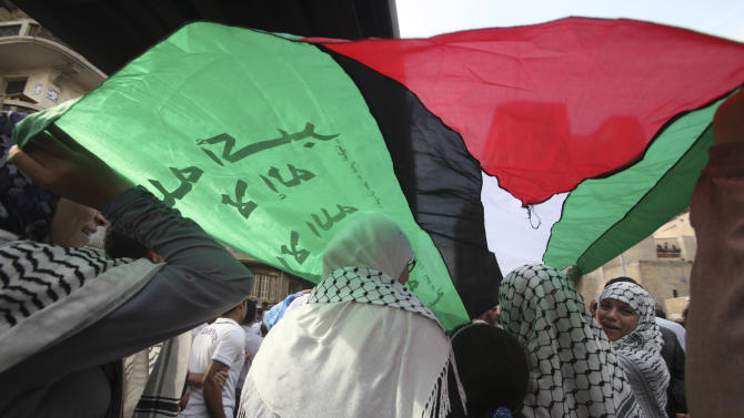 Protesters chant slogans and wave Palestinian flags during a march against the Israeli invasion of Gaza, through the streets towards Tahrir square after Friday prayers in Cairo, Egypt, Friday, Nov. 16, 2012. In his Friday sermon at Al-Azhar mosque, influential cleric Sheikh Yusuf al-Qaradawi, not shown, said the Islamic world would not be silent in the face of Israel's military operation in Gaza. (AP Photo/Thomas Hartwell)