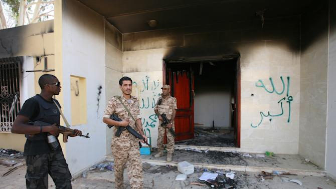 FILE - In this Friday, Sept. 14, 2012 file photo, Libyan military guards check one of the U.S. Consulate's burnt out buildings during a visit by Libyan President Mohammed el-Megarif, not shown, to the U.S. Consulate to express sympathy for the death of the American ambassador, Chris Stevens and his colleagues in the deadly attack on the Consulate last Tuesday, September 11, in Benghazi, Libya. Libya's upheaval the past two years helped lead to the ongoing conflict in Mali, and now Mali's war threatens to wash back and further hike Libya's instability. There is a growing fear that post-Moammar Gadhafi Libya is becoming an incubator of turmoil, with an overflow of weapons and Islamic jihadi militants operating freely, ready for battlefields at home or abroad.(AP Photo/Mohammad Hannon, File)