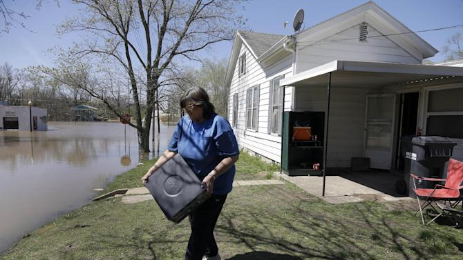 Brenda Scranton helps move belongings out of her son's rented house as floodwater slowly rises around it Saturday, April 20, 2013, in Louisiana, Mo. Scranton's son, Richard Campbell and his family, plan to leave the house, which flooded in 1993 and 2008, and not return. (AP Photo/Jeff Roberson)