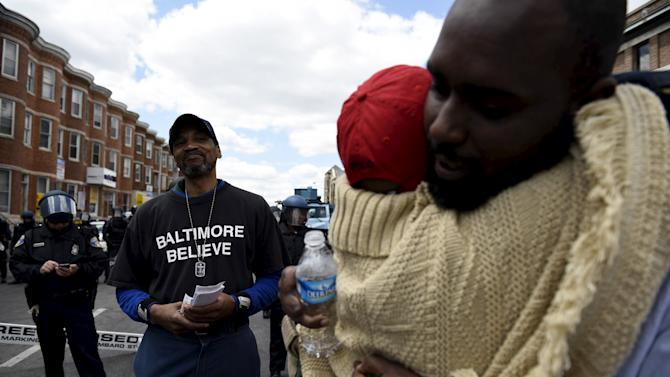Two protesters hug each other after a debate near the CVS Pharmacy building on Pennsylvania Avenue in Baltimore