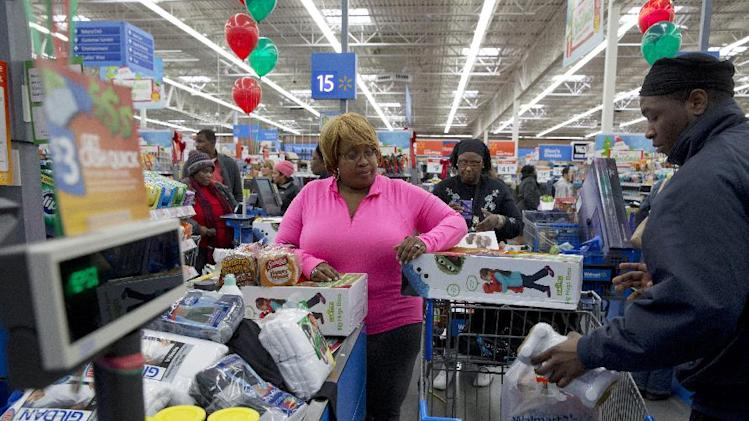 "FILE - In this Wednesday, Dec. 4, 2013, file photo, April Taylor of Upper Marlboro, Md., left, buys items from groceries to Christmas presents with her son Jarhon Taylor, right, on opening day of a new Wal-Mart on Georgia Avenue Northwest in Washington. Wal-Mart told The Associated Press Friday, March 21, 2014, that it has rolled out an online tool that allows shoppers to compare its prices on 80,000 food and household products to those of its competitors. The world's largest retailer began offering the feature that's called ""Savings Catcher"" on its website last month in seven big markets that include Dallas, San Diego and Atlanta. (AP Photo/Jacquelyn Martin, File)"