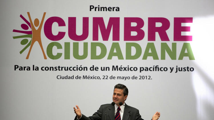 "Enrique Pena Nieto, presidential candidate for the Institutional Revolutionary Party (PRI), speaks during the first Citizens Summit in Mexico City, Tuesday, May 22, 2012. Mexico will hold presidential elections on July 1. The sign behind reads in Spanish ""For the construction of a fair and just Mexico."" (AP Photo/Eduardo Verdugo)"