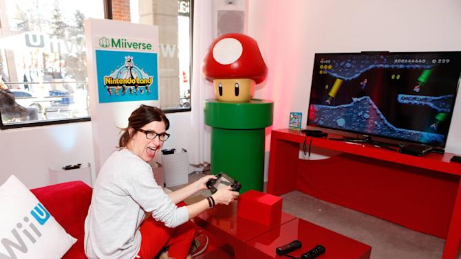 Actress Kathryn Hahn warms up and checks out Wii U at the Nintendo Lounge while playing New Super Mario Bros. U during a break from the Sundance Film Festival on Sunday, Jan. 20, 2013 in Park City, UT. (Photo by Todd Williamson/Invision for Nintendo/AP Images)