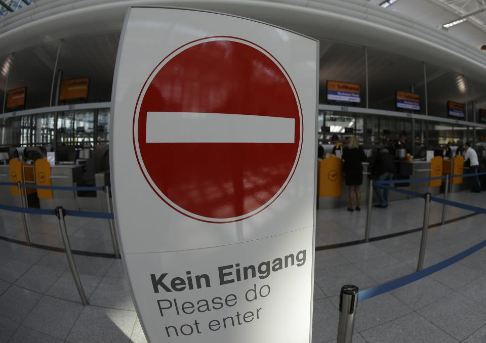 Passengers stand behind an exit sign near Lufthansa counters as flight attendants of German Lufthansa airline went on an 24-hour-strike for higher wages at the airport in Munich, southern Germany, on Friday, Sept. 7, 2012. (AP Photo/Matthias Schrader)
